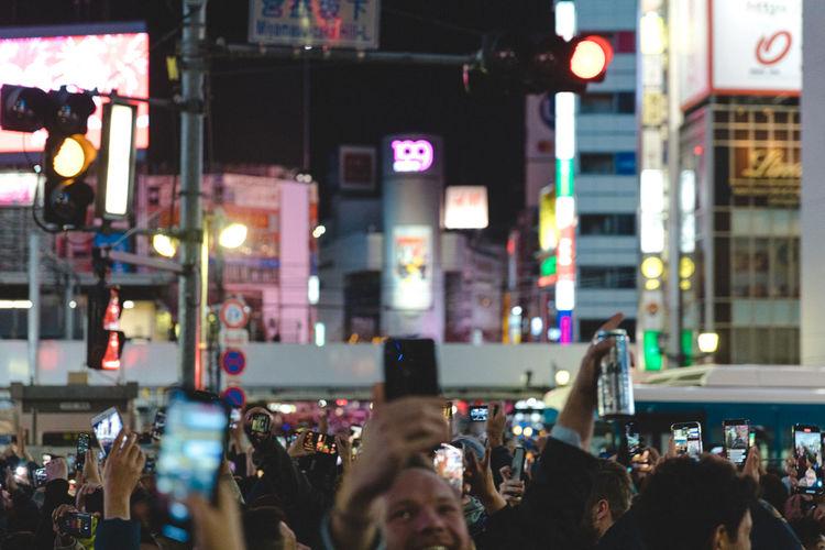 People photographing illuminated city street at night