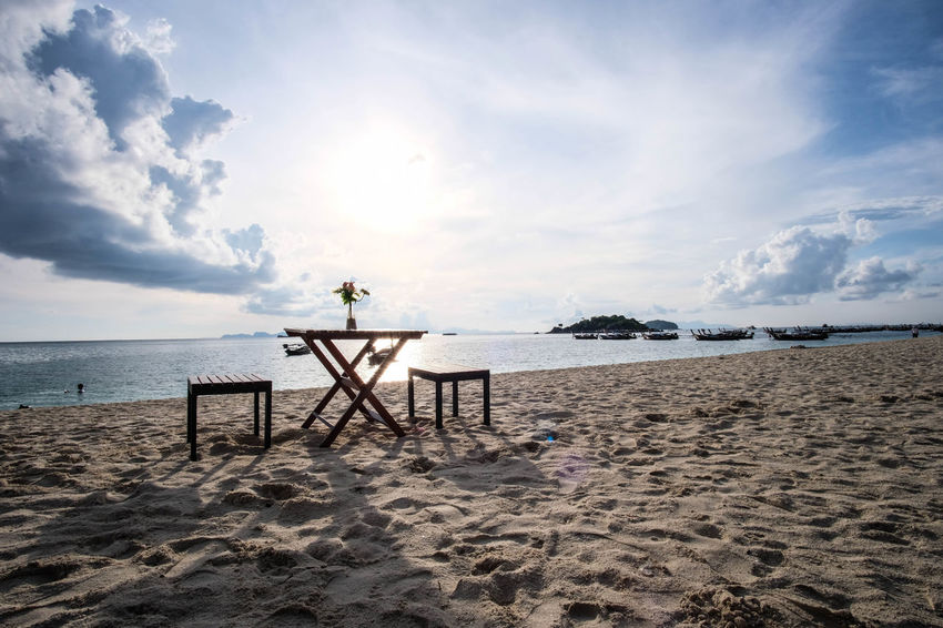 A beautiful cloudy sky and sunlight reflection on the sea; A flower in the vase on the wooden table and two wooden seats on the beach. Reflection Sunlight Travel Beach Horizon Over Water Island Landscape Nature Outdoors Relaxation Sand Scenics Sea Seascape Shadow Sky Summer Sunrise Sunset Vacation