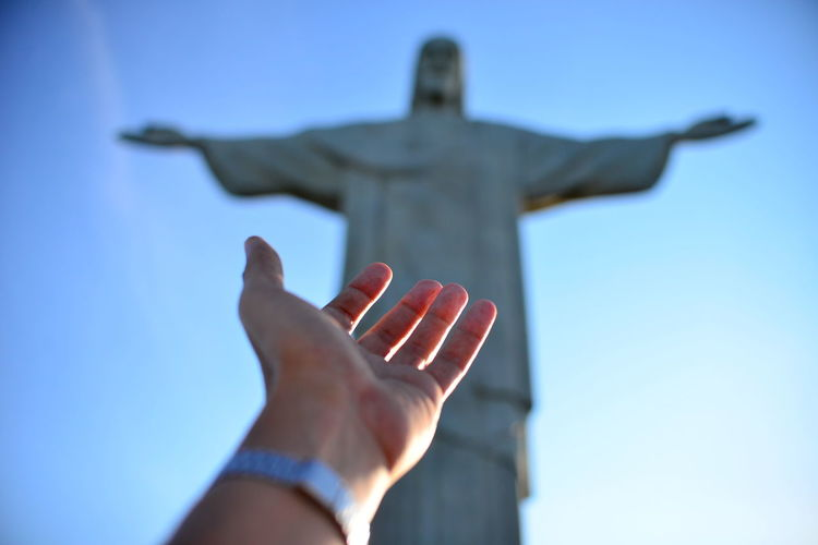 Low angle view of human hand against christ the redeemer