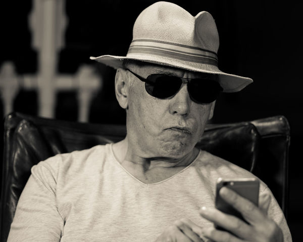 The Secret Life Of Don Giancarlo (Series of Selfies; Hat, Cap, Scarf, Eyeglasses, sunglasses, Mobile Phone, three point lighting, Pentax K-1 on tripod remote control via Smartphone App) Acting Hat Mobile Phone Old Man Sitting Storytelling Acting Crazy Day Expressions Feelings Focus On Foreground Hat One Person People Real People Scarf Sceptical Look Selfie Series Sunglass  Sunglasses