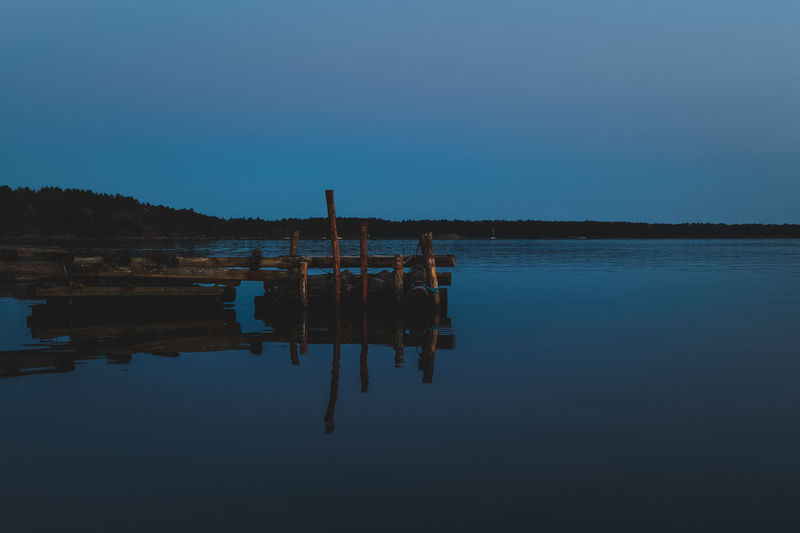 Reflection of wooden post in lake against clear blue sky
