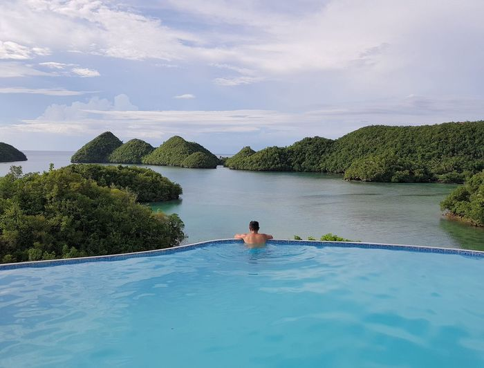 Rear view of man swimming in infinity pool by sea against sky