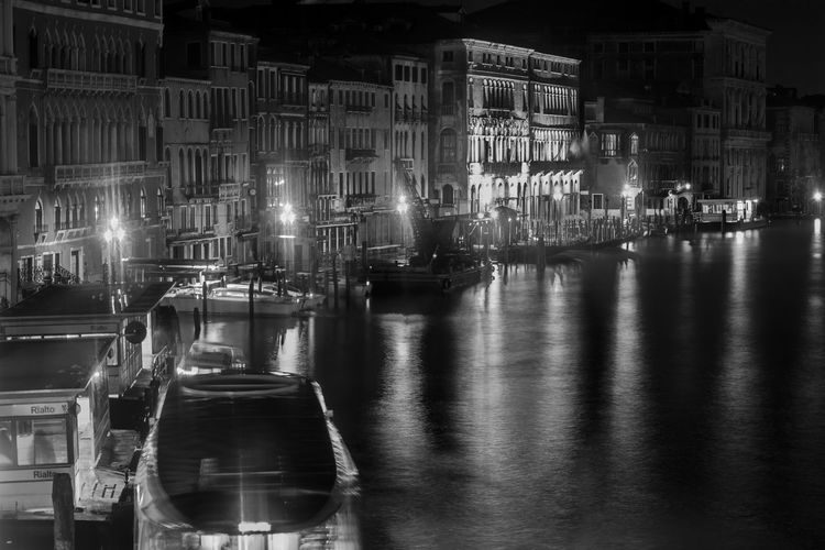 Illuminated harbor by buildings in city at night