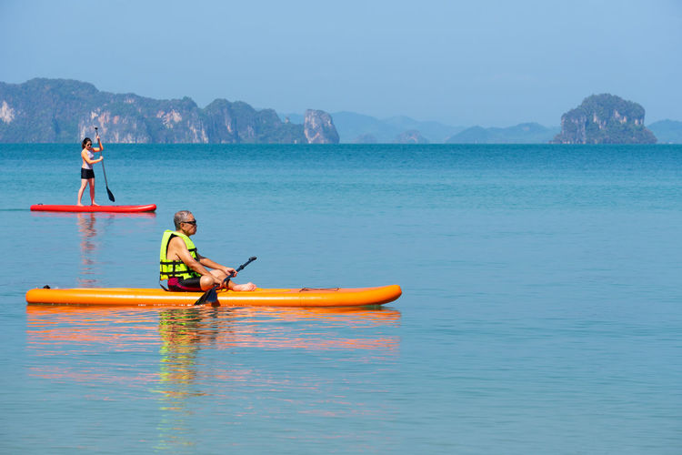 Asian senior father playing standing up paddle board daughter at blue sea on summer vacation