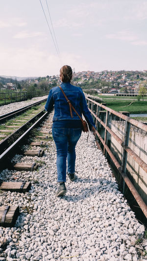 Rear view of woman walking by railroad track