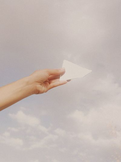 Low angle view of hand holding paper against sky