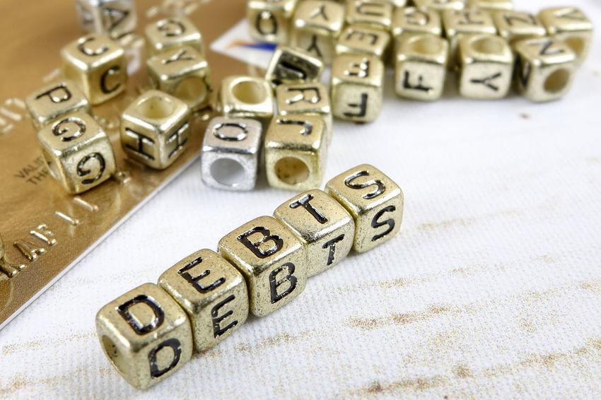 DEBT CONCEPT WITH GOLD DICE ON A WOODEN TABLE Arts Culture And Entertainment Close-up Communication Credit Card Debt Crisis Dice Finance Gambling Game Of Chance High Angle View Indoors  Large Group Of Objects Leisure Activity Leisure Games Letter No People Number Still Life Studio Shot Table Text Wealth Western Script