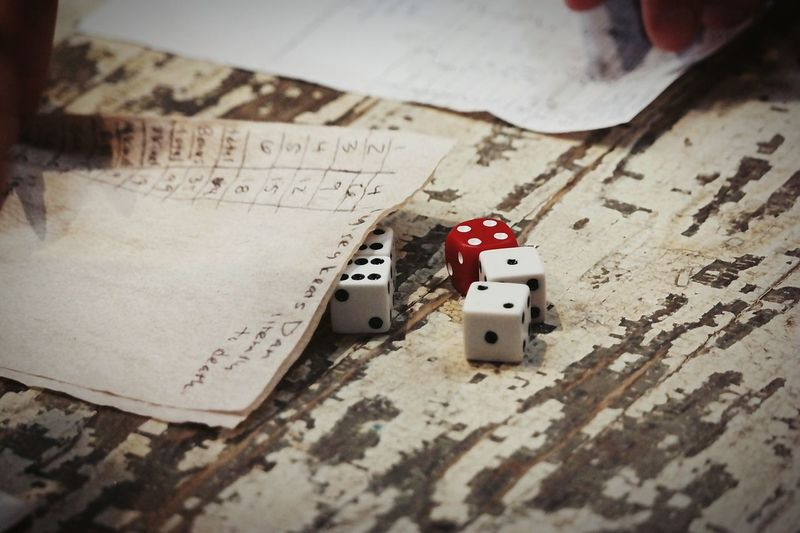 High Angle View Of Dice By Papers On Wooden Table