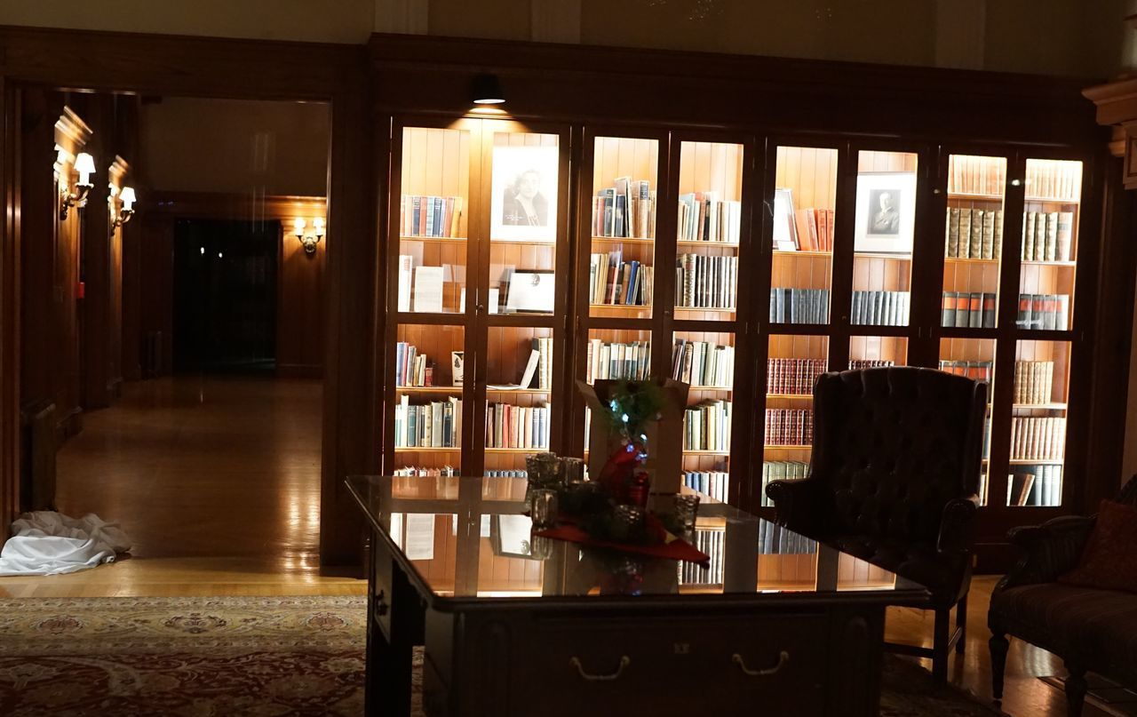 table, indoors, shelf, bookshelf, seat, chair, furniture, window, publication, book, no people, home interior, glass - material, transparent, domestic room, architecture, absence, wood - material, illuminated, library, luxury