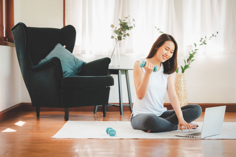Woman using phone while sitting on chair at home
