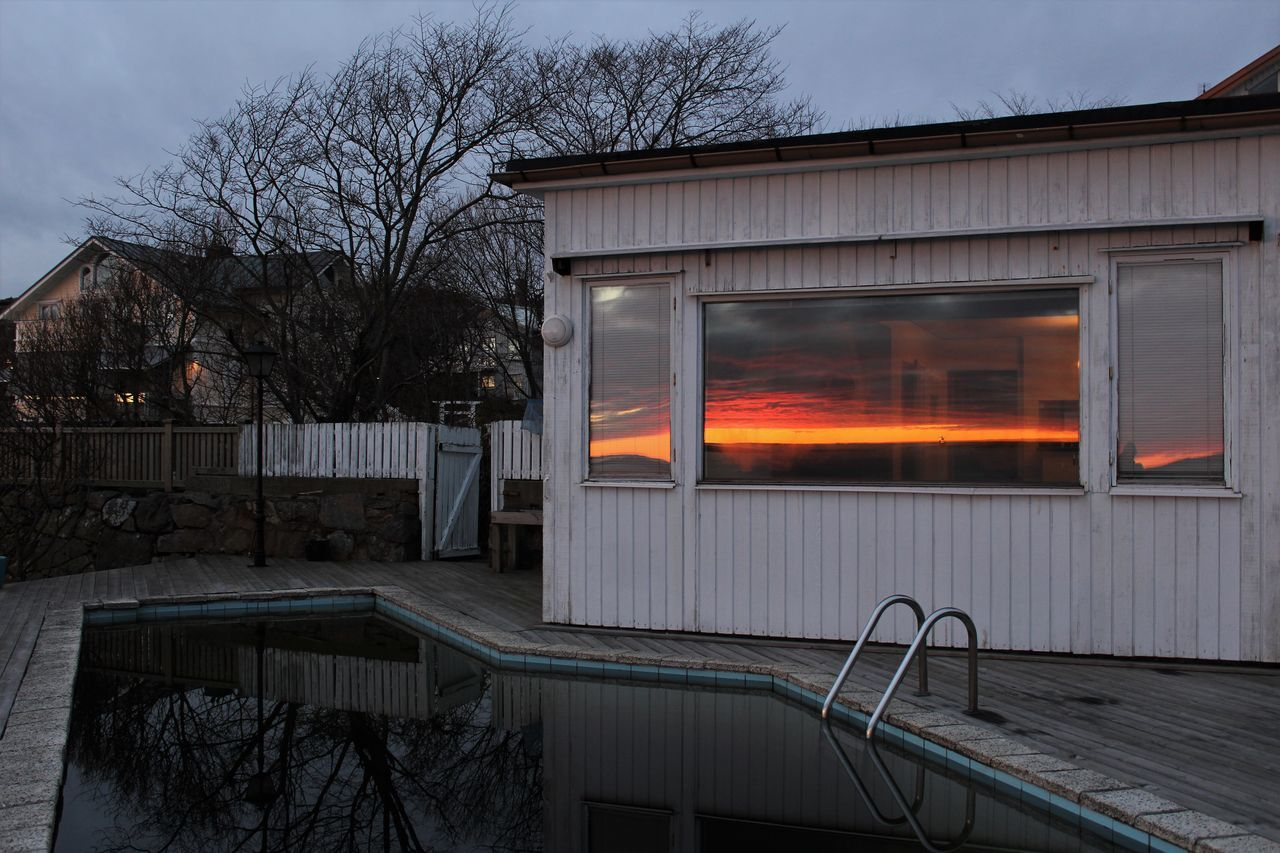 Swimming pool by house with reflection of orange sky on glass window