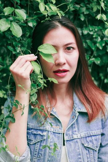 Portrait of beautiful young woman with leaves outdoors