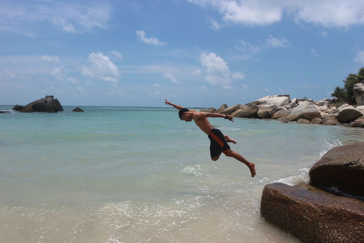 Man jumping on rock in sea against sky