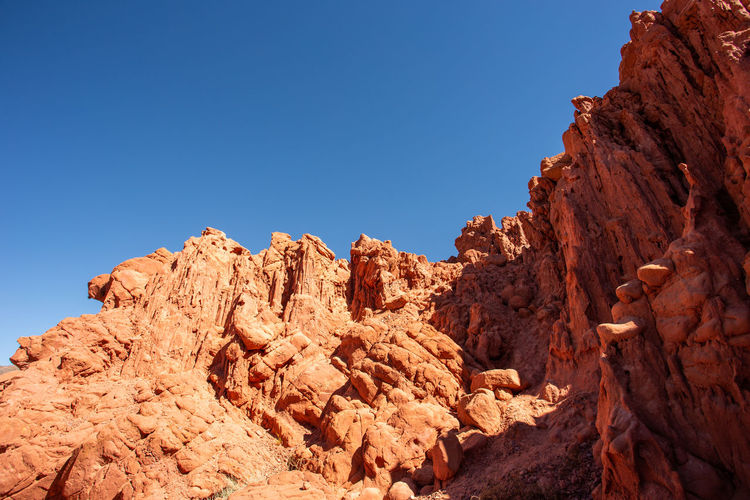 Low angle view of rock formations against clear blue sky