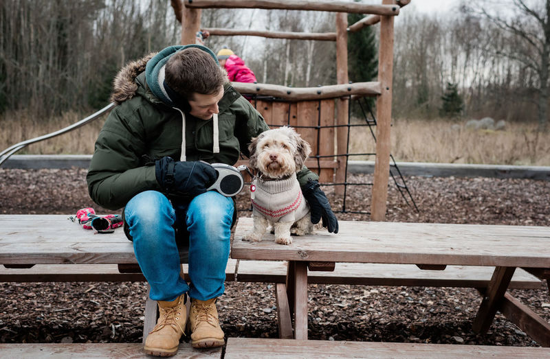 Man with dog sitting on bench