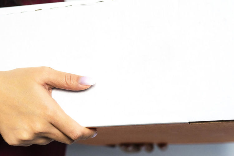Midsection of person holding paper against white wall