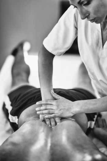 Woman Massaging Man Lying On Bed