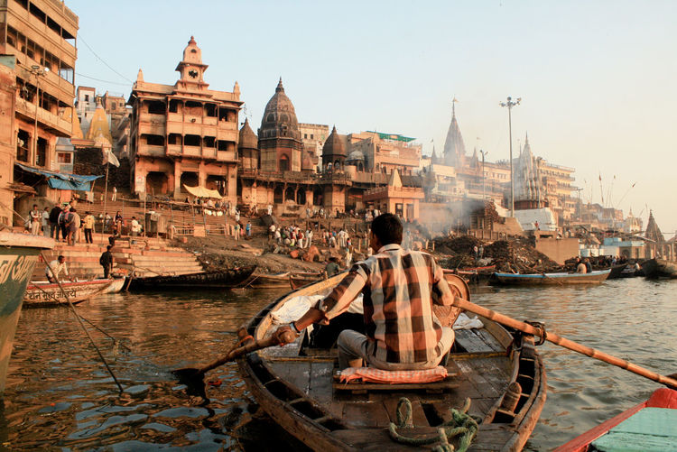 Rear view of man sailing boat on ganges river by temples