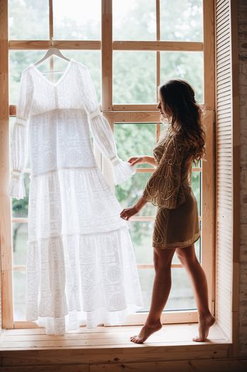 Side view of woman looking at white dress hanging on window at home