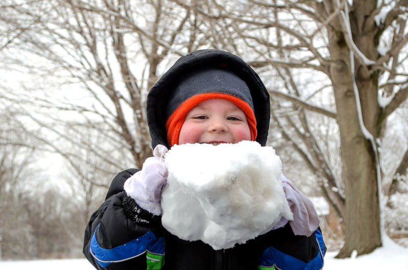 Portrait Of Smiling Cute Boy Playing With Snow During Winter