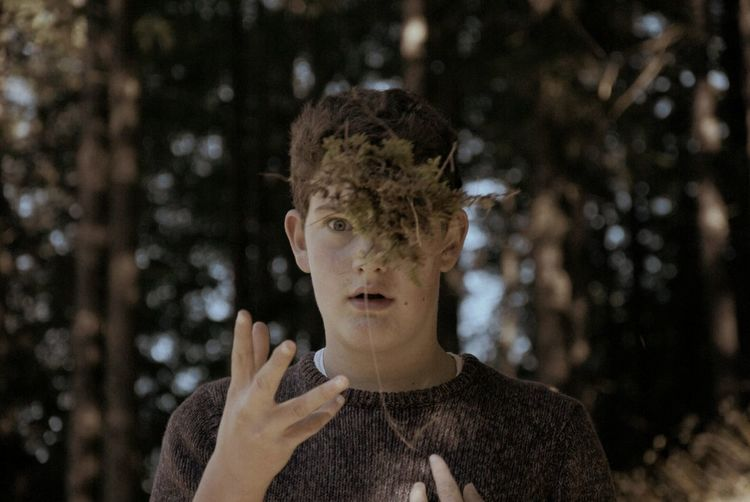 Portrait Of Young Man Throwing Leaves