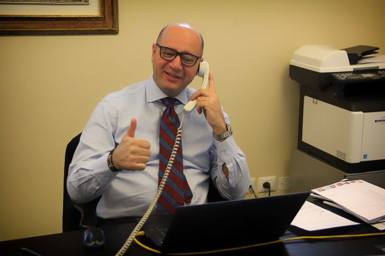 Happy manager gesturing thumbs up while talking on phone in office