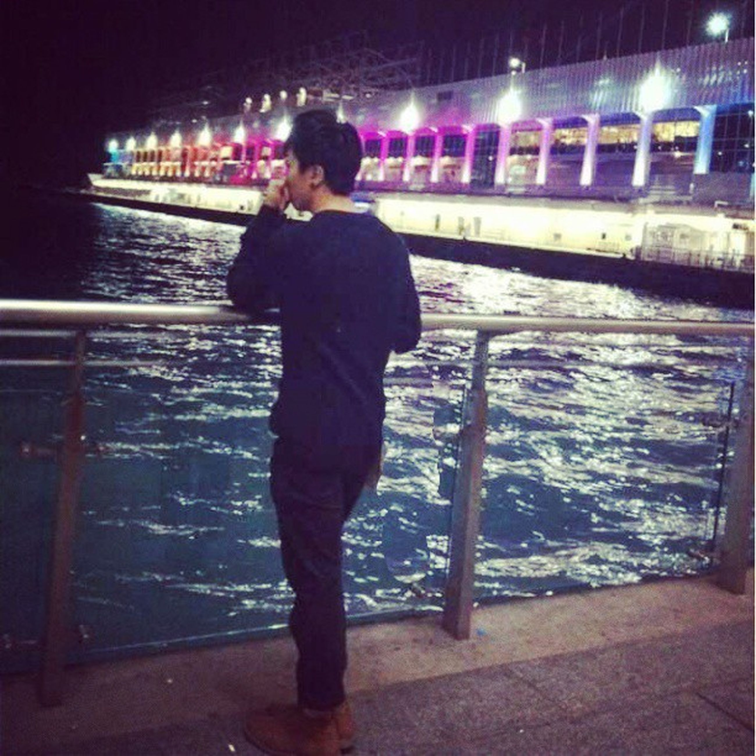 night, full length, illuminated, lifestyles, standing, rear view, casual clothing, leisure activity, three quarter length, men, railing, built structure, water, indoors, architecture, walking, transportation, reflection