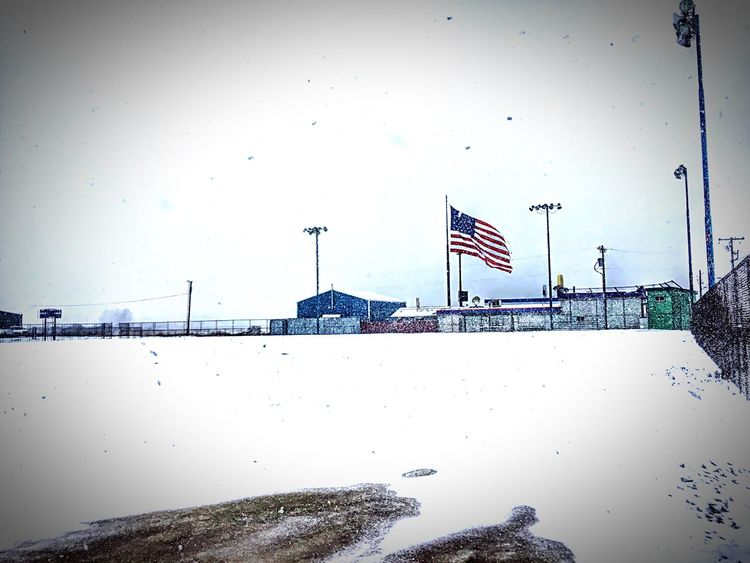 """These Colors Don't Run"" The red, white and blue flying near a baseball field even in a snow storm. Smalltown Smalltownlife Smalltownusa Americanflag Snowstorm American Route 66 Redwhiteandblue AmericanPride Baseball Field"