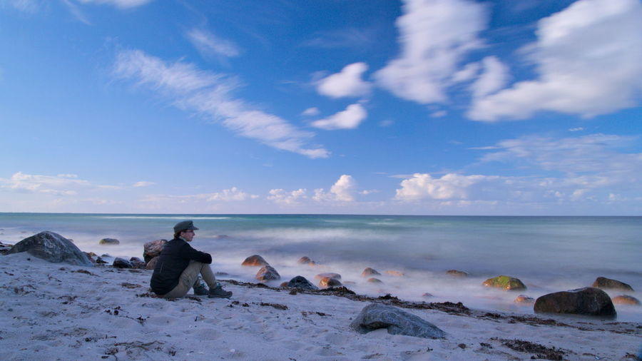 Side View Of Man Sitting On Baltic Sea Shore Against Sky
