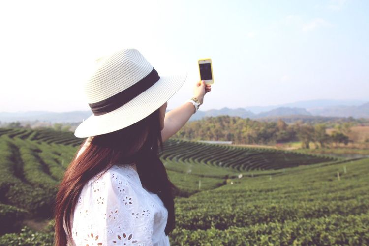 Side View Of Woman Photographing Farm Through Smart Phone