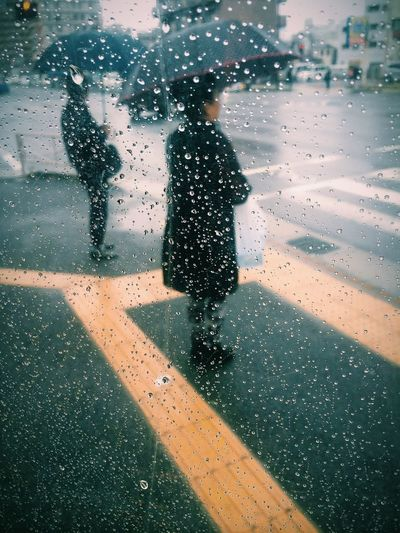 Two people covering umbrellas viewed through windshield with raindrops