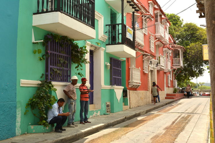 Residential District Vivid Colours  Blue Turquoise Colored Men Working Work Lifestyles Balcony Uphill Street Streetphotography Sidewalk Colombia Cartagena Latin America Travel Travel Destinations Travel Photography Local People Salmon Colored