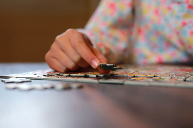 Child working on jigsaw puzzle. Child holding a puzzle in hands. One Person Selective Focus Midsection Indoors  Human Body Part Arts Culture And Entertainment Close-up Adult Table Hand Holding Leisure Activity Human Hand Skill  Casual Clothing Offspring Day Sitting Surface Level Human Limb Jigsaw Puzzle Jigsaw Piece