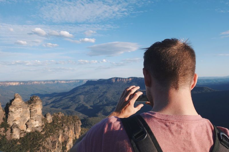 Rear view of man photographing mountain through camera