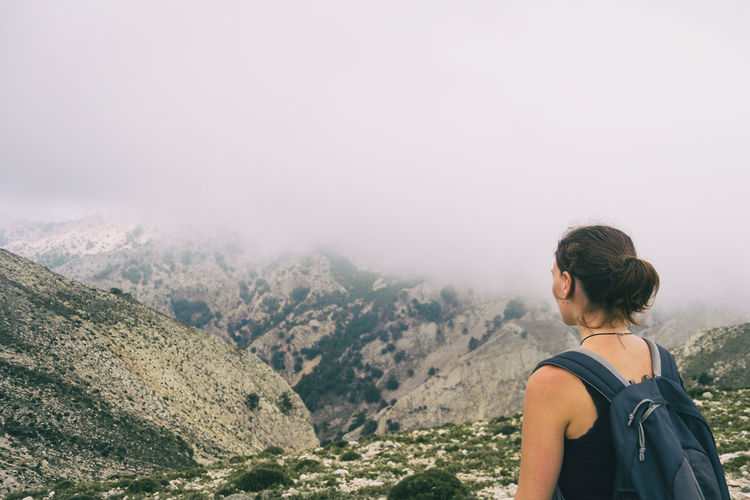 Woman hiking on a mountain path in catalonia on a cloudy summer day