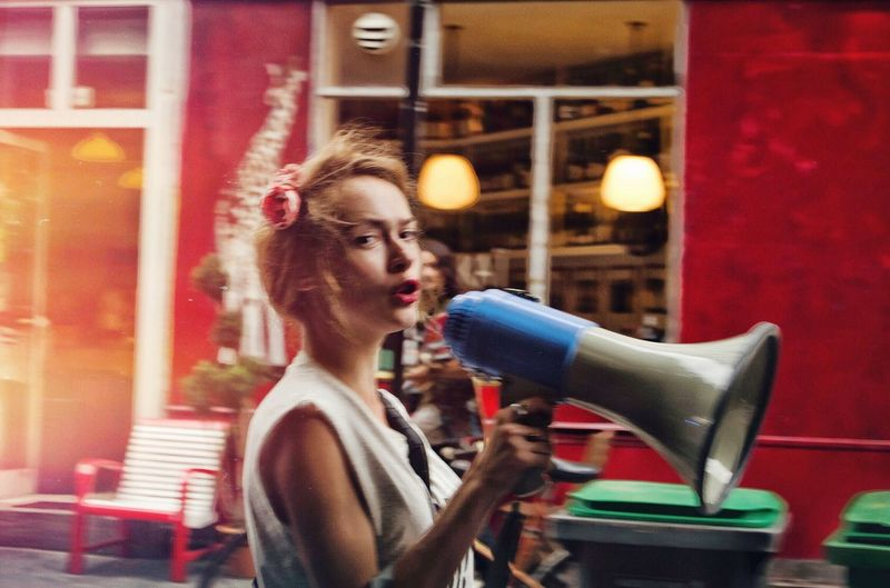 Woman talking through megaphone while standing by building