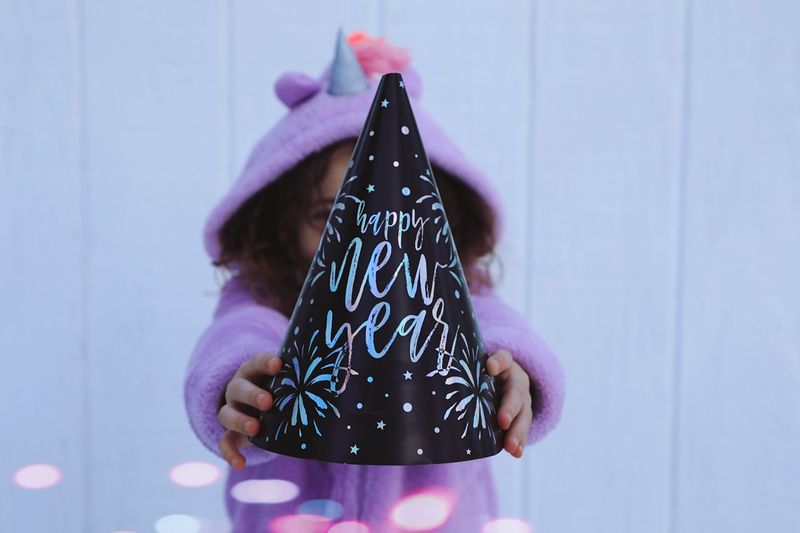 Close-up of girl holding party hat against wall