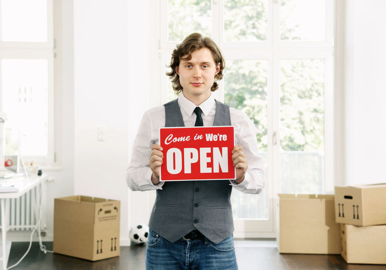 Man With Information Sign Standing At Office
