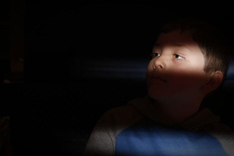 Cute boy looking away in darkroom