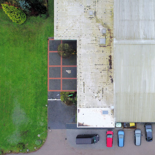 Cut vertical view from the air of an old, ugly tennis hall with parked cars in front of it, aerial view Aerial Shot Cars Drone  Drone Dji Drone Shot Orthogonal Pine Roof Rooftop Ugly Above Aerial Aerial Photography Aerial View Architecture Building Exterior Built Structure Day Dirty High Angle View Lawn Nature No People Outdoors Parking