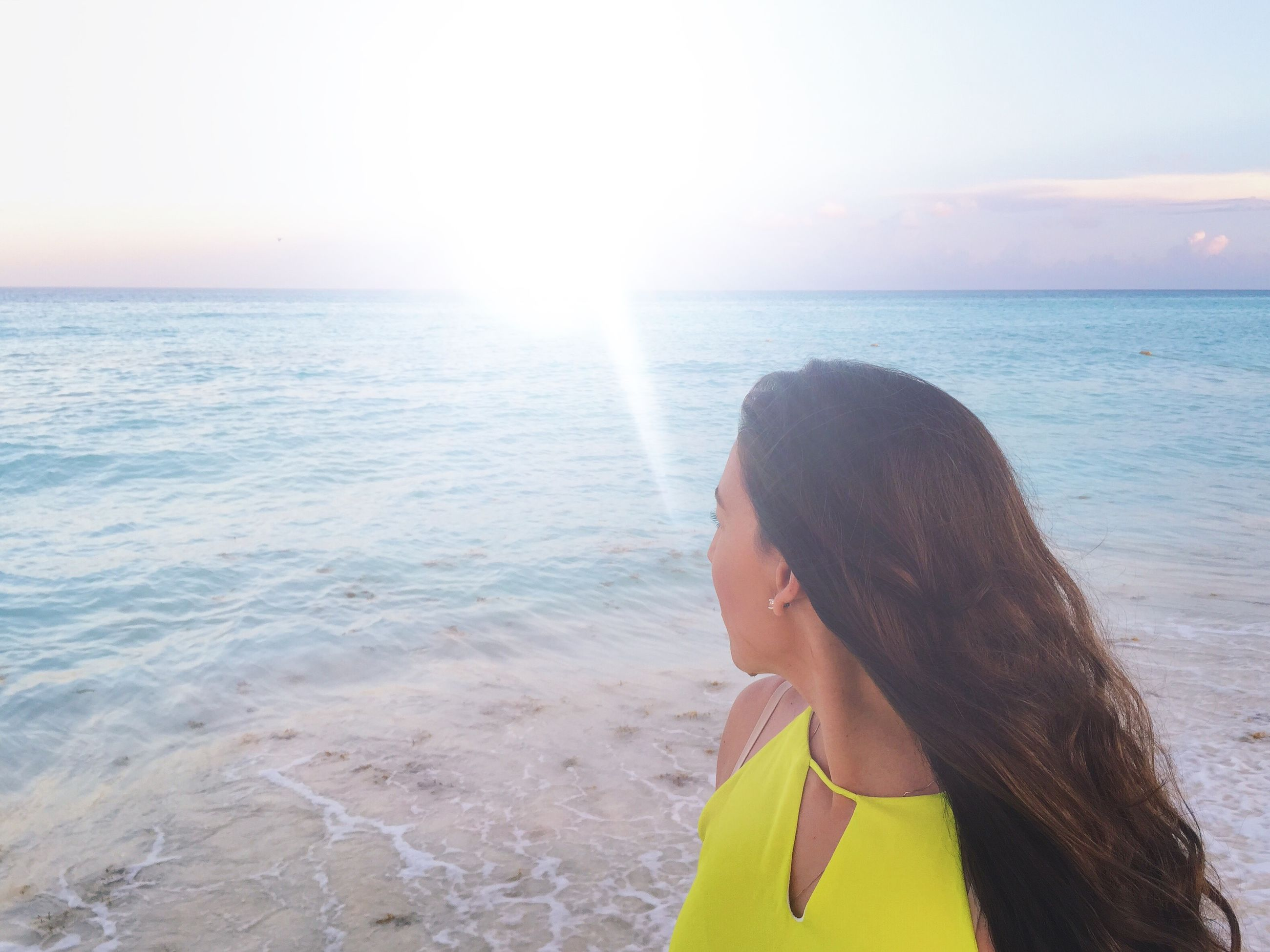 sea, horizon over water, water, lifestyles, beach, leisure activity, sky, young adult, beauty in nature, scenics, shore, sunlight, tranquil scene, nature, young women, vacations, tranquility, sun
