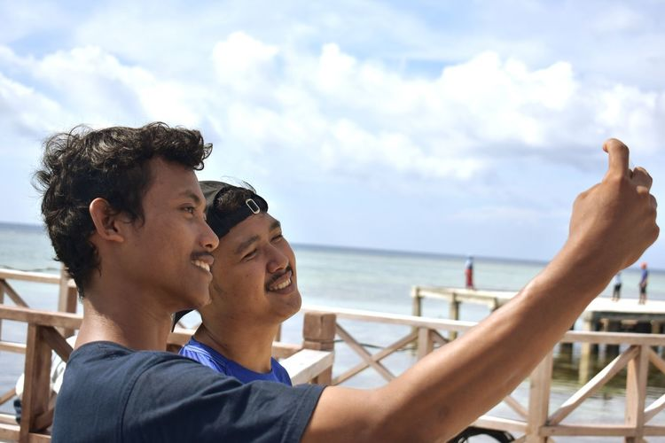 Friends taking selfie by sea against sky