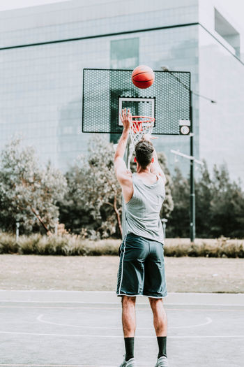 Rear view of man playing with basketball hoop