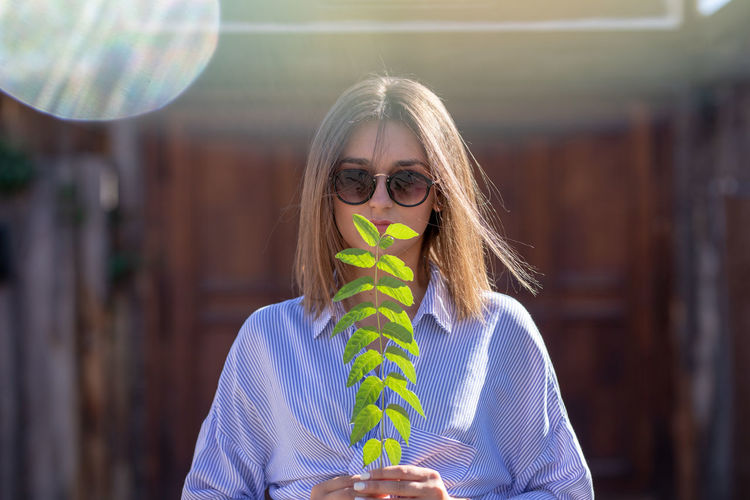 Portrait of woman in sunglasses holding plant