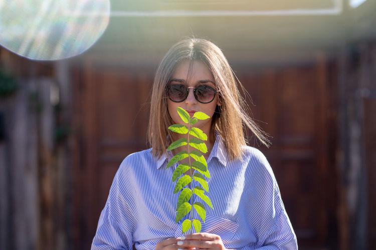 Portrait of woman holding sunglasses