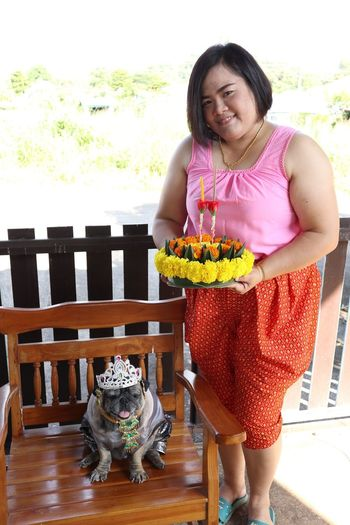 Portrait of smiling woman with dog holding cake while outdoors