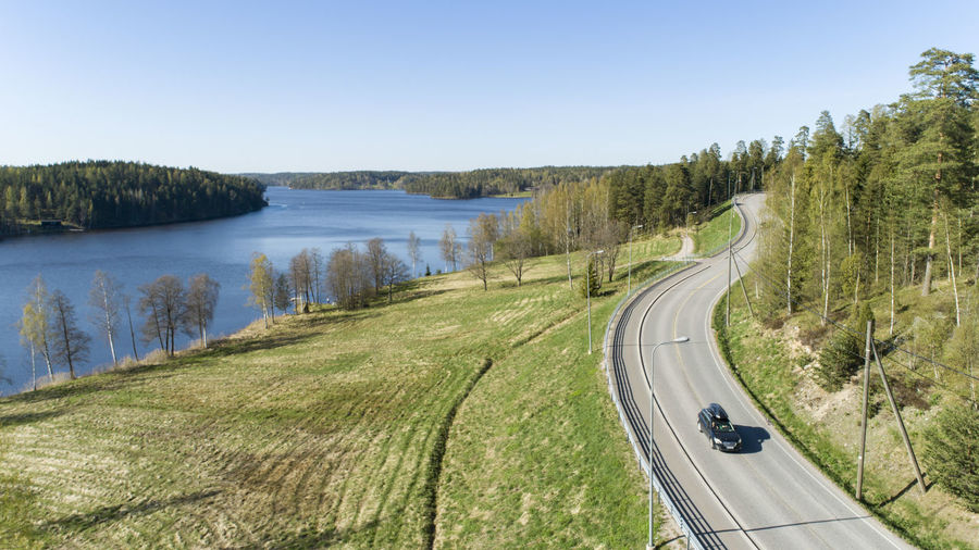 Panoramic view of road by lake against clear sky