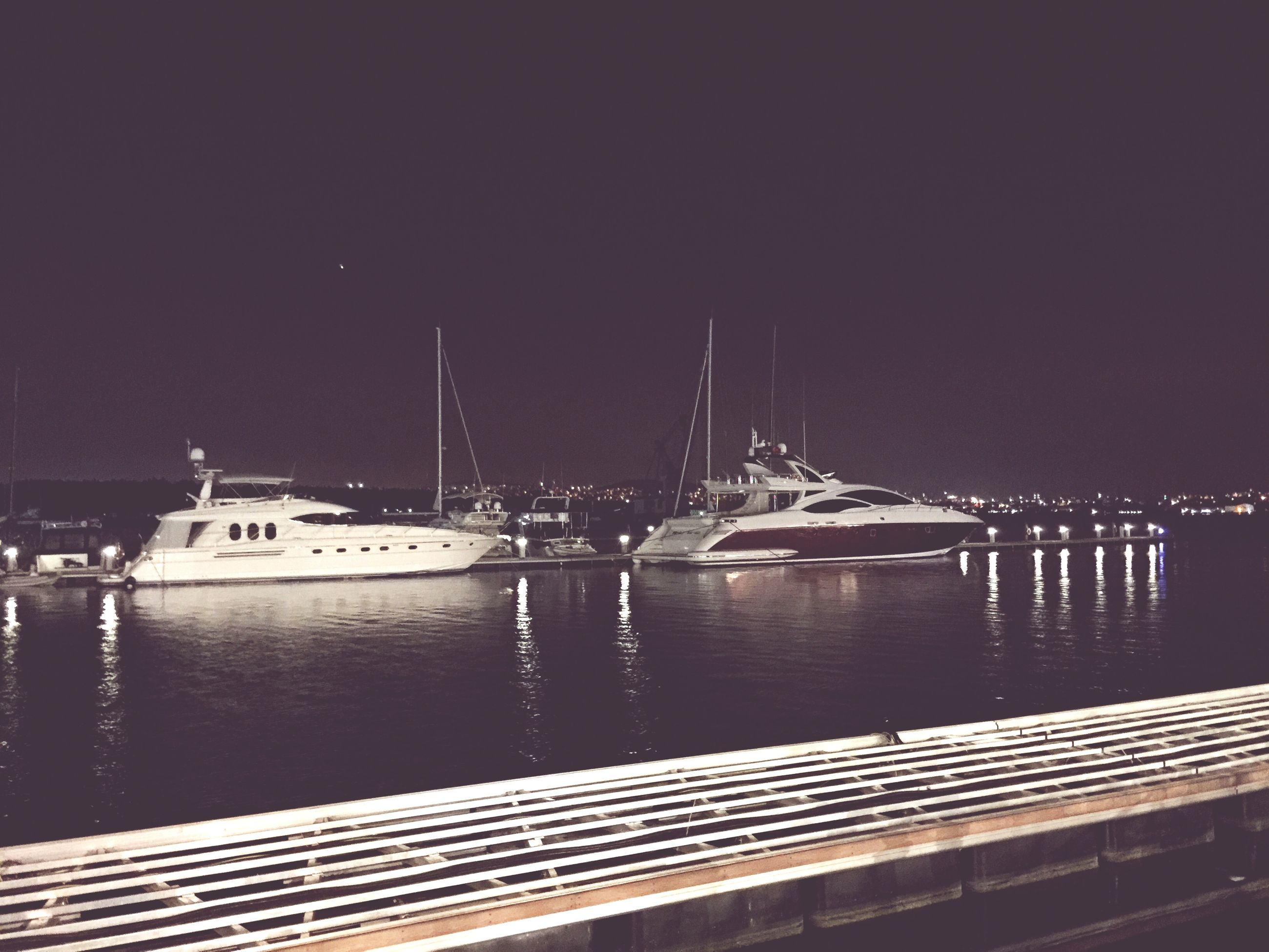 water, night, illuminated, transportation, clear sky, built structure, railing, river, reflection, architecture, nautical vessel, bridge - man made structure, connection, pier, copy space, sea, street light, bridge, boat, sky