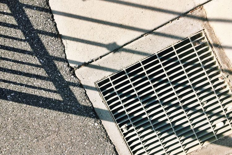 Grate Shadow Sunlight Pattern Day Metal Nature High Angle View Security No People Footpath Safety Outdoors Protection Street Focus On Shadow Grid City Sunny Grate Paving Stone 17.62°