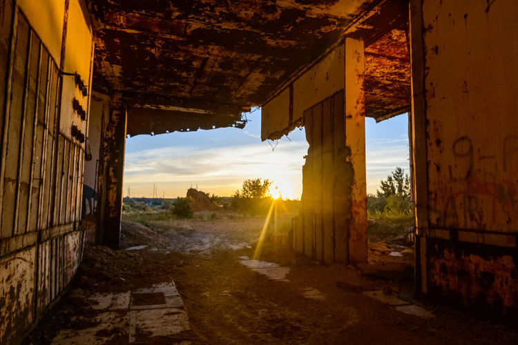 Abandoned buildings against sky during sunset